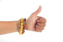 Femme de main gauche montrant les pouces et le bracelet sur le backgrou blanc Photographie stock libre de droits
