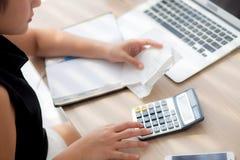 Femme de main de plan rapproché calculant le ménage de dépenses et écrivant le carnet sur le bureau, fille vérifiant la facture e photographie stock libre de droits