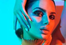 Femme de mannequin dans les lumières lumineuses colorées avec le maquillage à la mode posant dans le studio Image libre de droits