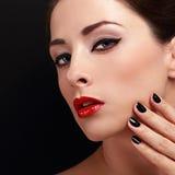 Femme de maquillage avec les lèvres rouges et le vernis à ongles noir Image libre de droits