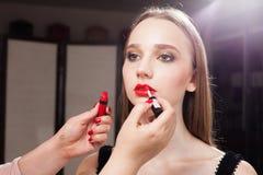 Femme de maquillage mettant le lustre rouge de lèvre sur une femme images libres de droits