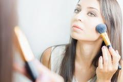 Femme de maquilleur faisant le maquillage utilisant la brosse cosmétique pour vous-même Photo stock