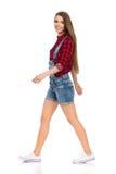 Femme de marche dans des shorts de jeans regardant l'appareil-photo Image stock