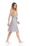Femme de marche dans la robe et des espadrilles blanches d'été Photo libre de droits