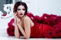 Femme de modèle de brune de beauté en égalisant la robe rouge Maquillage de luxe et coiffure de belle mode images libres de droits