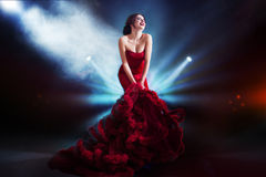 Femme de modèle de brune de beauté en égalisant la robe rouge Maquillage de luxe et coiffure de belle mode Fond foncé, lumière Photo libre de droits