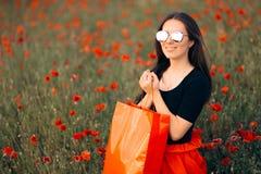 Femme de mode avec des sacs à provisions entourés par des pavots images libres de droits