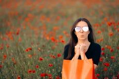 Femme de mode avec des sacs à provisions entourés par des pavots images stock