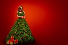 Femme de mode dans la robe d'arbre de Noël, présent modèle de Noël de prise image libre de droits