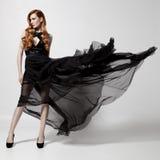 Femme de mode dans la robe noire de flottement Fond blanc Photos stock