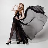 Femme de mode dans la robe noire de flottement Fond blanc Images stock