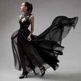 Femme de mode dans la robe noire de flottement Fond gris Images libres de droits