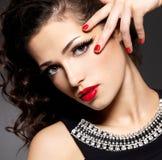 Femme de mode de beauté avec les clous rouges et le renivellement photographie stock libre de droits