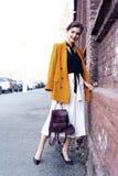 Femme de mode de portrait marchant sur la rue Elle utilise la gu?pe, souriant pour d?grossir photo stock