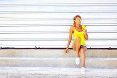 Femme de mode posant au-dessus du mur Blonde à la mode de sourire d Photo stock