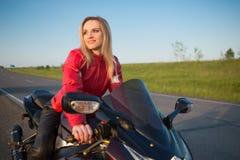 Femme de motard s'asseyant sur une moto Photographie stock