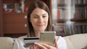 Femme de mouvement lent dans le chemisier blanc se reposant sur le sofa dans le salon achetant en ligne avec la carte de crédit s banque de vidéos