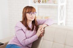Femme de Moyen Âge détendant sur le fond de sofa à la maison ménopause Copiez l'espace et raillez  Fête des mères Photo stock