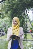 Femme de muslimah de visage de sourire jeune tenant et tenant des carnets en parc Photos stock