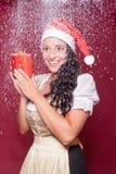 Femme de Noël dans le dirndl avec le paquet pendant les chutes de neige photo libre de droits