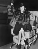 Femme de ondulation s'asseyant sur la pile du bagage (toutes les personnes représentées ne sont pas plus long vivantes et aucun d photos stock