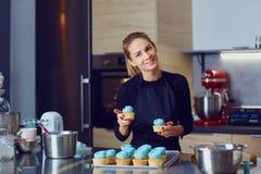 Femme de pâtisserie de confiseur tenant un plateau des petits gâteaux photo libre de droits