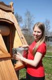 Femme de pays au bien avec un seau de l'eau Images stock