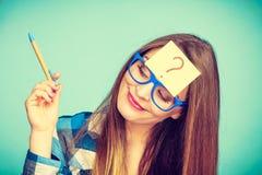 Femme de pensée avec de grandes lunettes et ampoule images stock