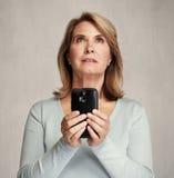 Femme de pensée avec le smartphone Photos stock