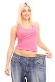 Femme de perte de poids avec de vieilles paires de jeans photos libres de droits