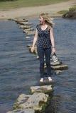 Femme de pierres de progression marchant nu-pieds à travers l'eau froide Images libres de droits