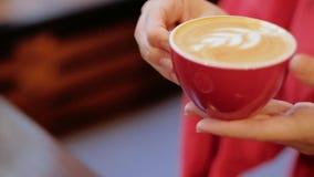Femme de plaisir de café goûtant le latte mousseux de tasse rouge banque de vidéos