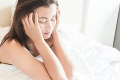 Femme de plan rapproché se réveillant avec la tête endolorie sur le lit, les soins de santé et le m Photo stock