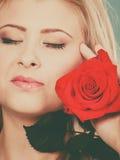 Femme de plan rapproché tenant la rose de rouge près du visage Image stock