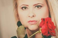 Femme de plan rapproché tenant la rose de rouge près du visage Photos stock