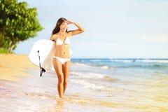 Femme de planche de surf marchant dans l'eau de plage Photos stock