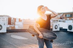 Femme de planchiste avec le longboard sur le coucher du soleil Image libre de droits