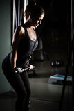 femme de poids de formation de gymnastique L'exercice dessus abaissent la machine de poids Femme faisant traction-UPS exerçant le Photo stock