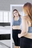 Femme de poids excessif avec le miroir dans la chambre à coucher Photographie stock