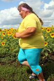 Femme de poids excessif courant le long du champ des tournesols Images libres de droits