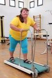 Femme de poids excessif courant sur le tapis roulant d'entraîneur Images stock