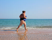 Femme de poids excessif exécutant sur la plage Images stock