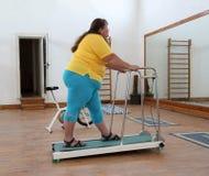 Femme de poids excessif exécutant sur le tapis roulant d'avion-école Images stock