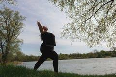 Femme de poids excessif faisant le yoga, d?tendant pr?s du lac images stock