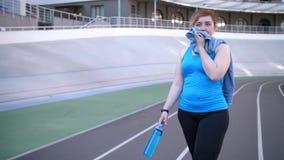 Femme de poids excessif fatiguée marchant après séance d'entraînement banque de vidéos