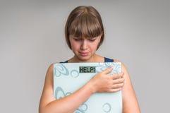 Femme de poids excessif frustrante tenant les échelles numériques avec l'AIDE ! Images stock