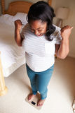 Femme de poids excessif heureuse se tenant sur des échelles dans la chambre à coucher Photographie stock