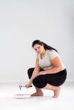 Femme de poids excessif heurtant l'échelle Image libre de droits