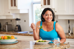 Femme de poids excessif mangeant le repas sain dans la cuisine Photos libres de droits
