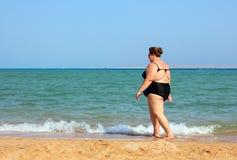 Femme de poids excessif marchant sur la plage Images libres de droits
